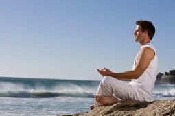 Young man meditating on a rock by the beach