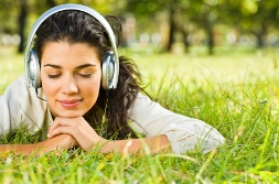 Young woman lying on grass listening to guided imagery on headphones